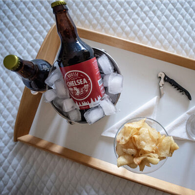 Wood tray with cup of chips, two drinks, and a bottle opener