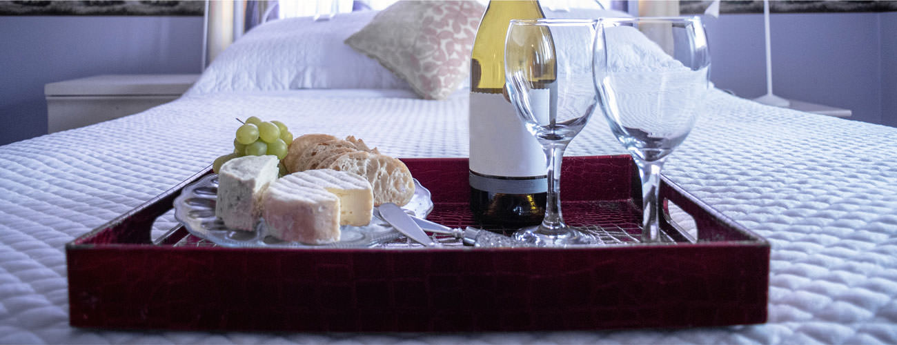 wood tray on a bed with wine and cheese